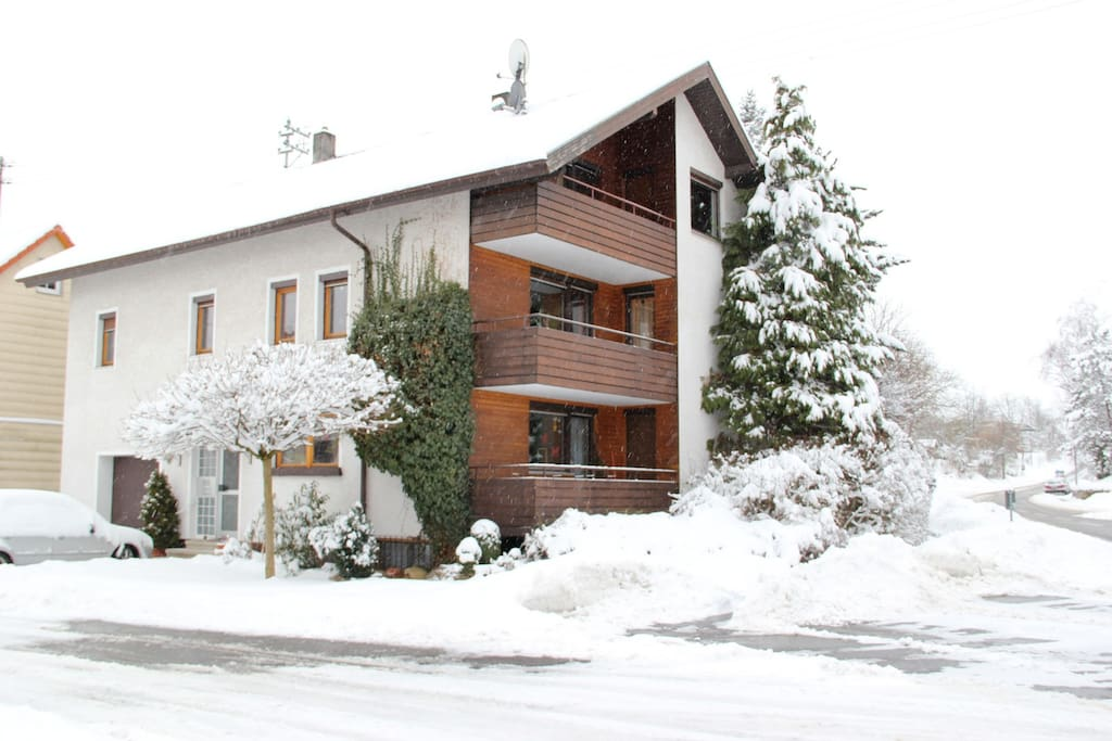 House in winter with snow; apartment is lower floor right