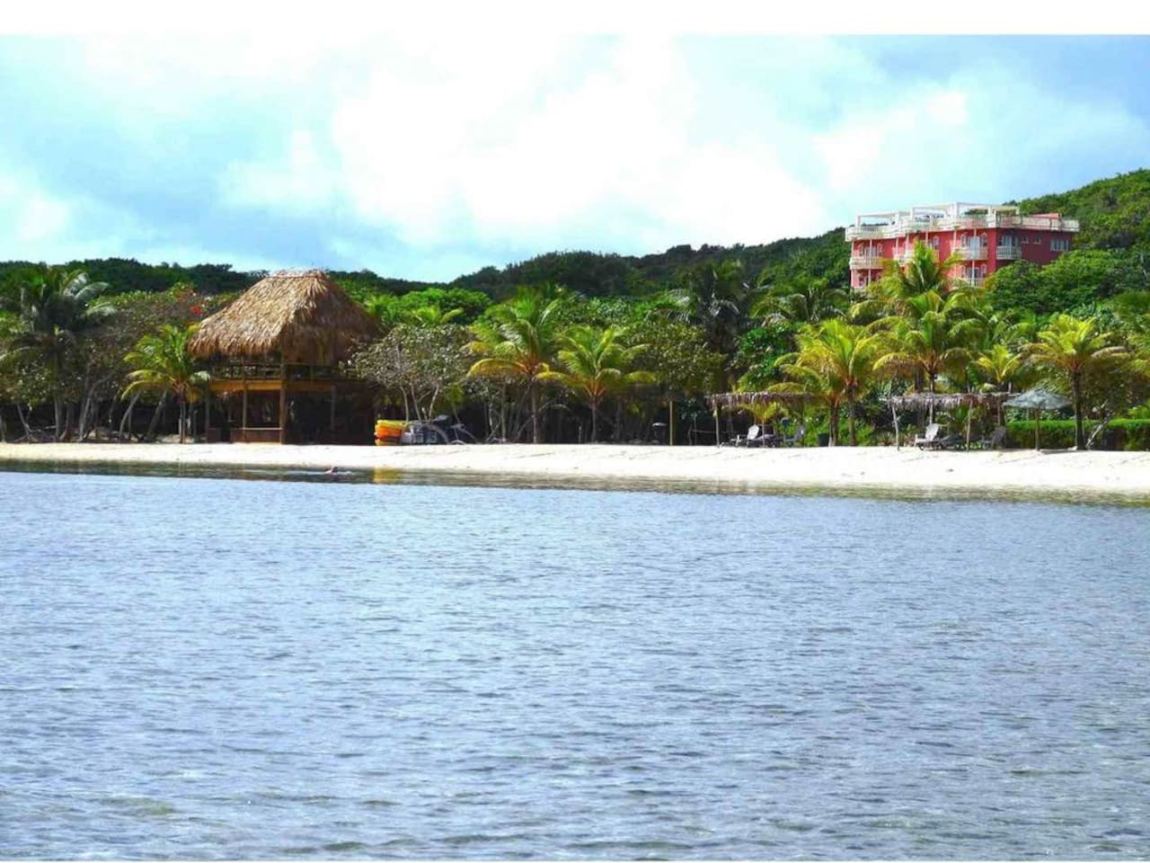 View of condo building, palapa & beach from seaside