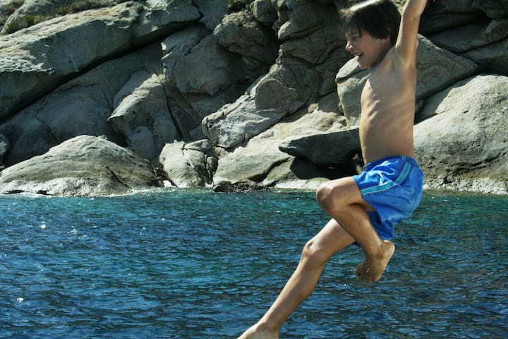 my son jumping in to the clear, warm turquoise water