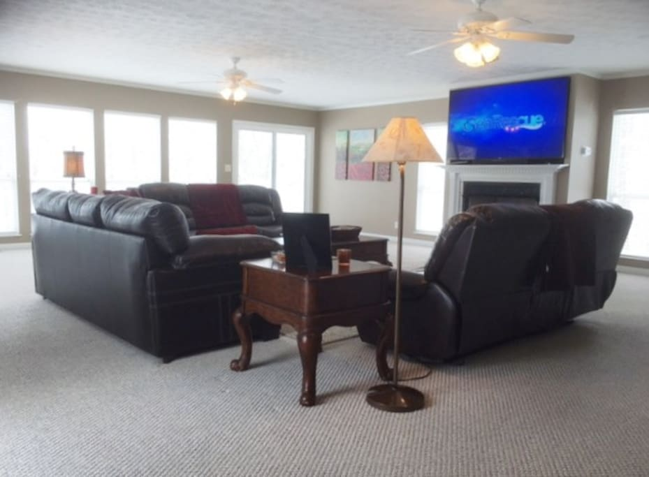 """Extra Large Family Room With 70"""" TV and Fireplace. Balcony leading to Outdoor Pool."""
