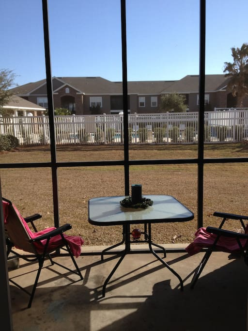 Screened in patio overlooks pool area