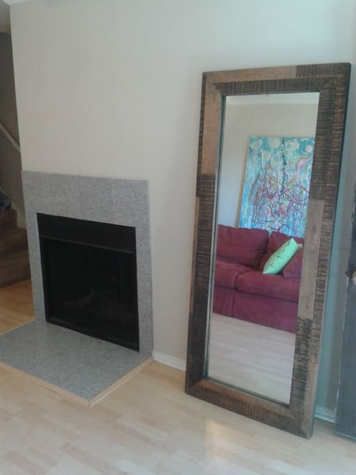 Fireplace for rare cold nights in Austin and reclaimed wood floor mirror.