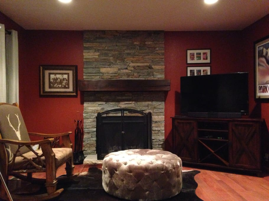 Living room features 46in cable HDTV with Bose soundbar, blu ray DVD player, wi-fi, board games and puzzles, rocking chair, plush ottoman, and a wood burning fireplace