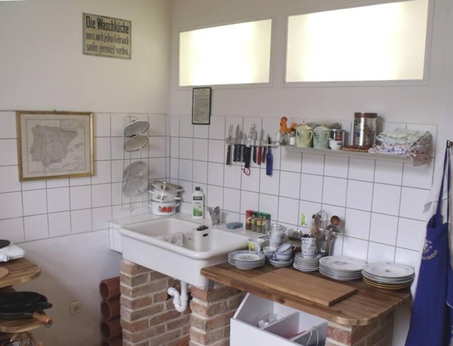 Waschbecken in der Küche, 2-Platten-Kochfeld und Kühlschrank gegenüber