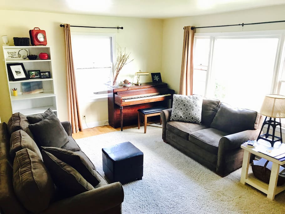 Full living room with piano and loveseat with a view.