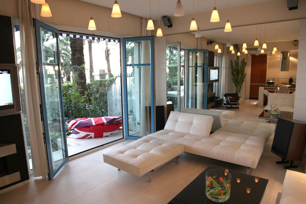 Living room with large sofas (convertible) and access to terrace and garden.