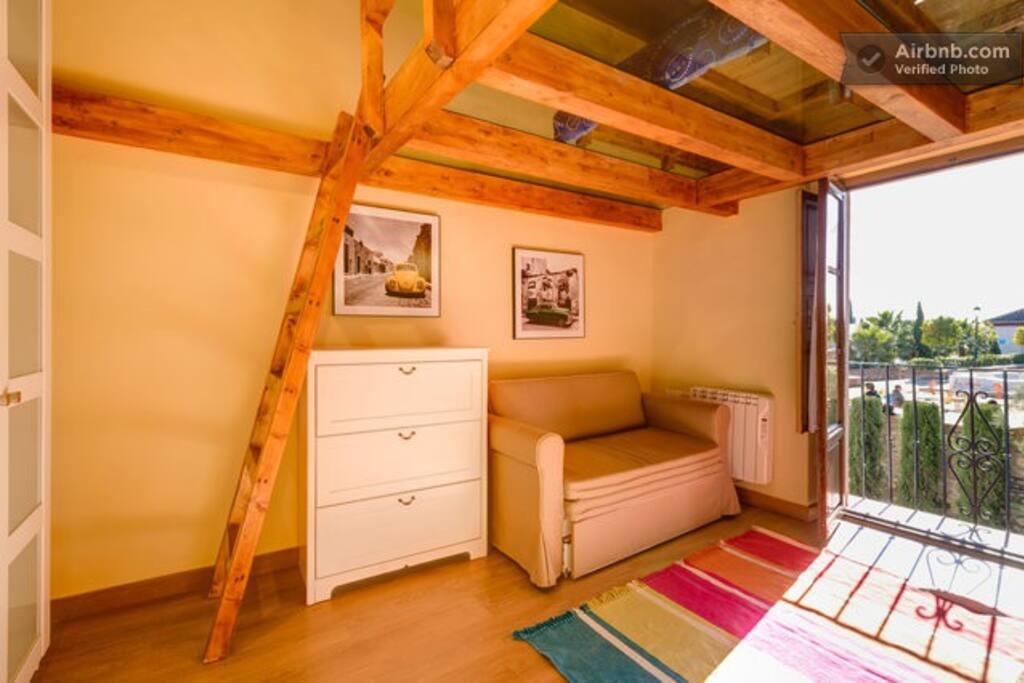 Dormitorio con cama en altillo con suelo de cristal