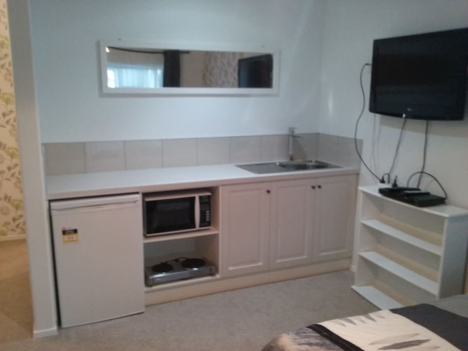 Kitchen showing fridge, microwave, hotplate and bench