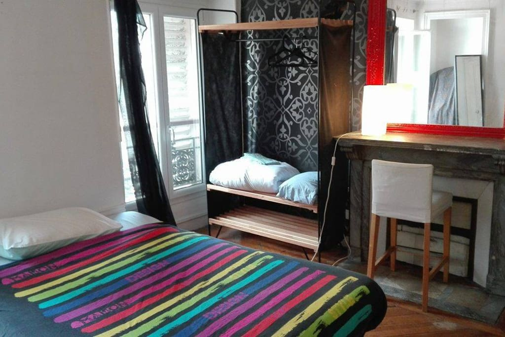 """Large bedroom of 20m2, bright, and """"très parisienne"""". Amazing view of Montmarte and Folies Bergere Theatre."""
