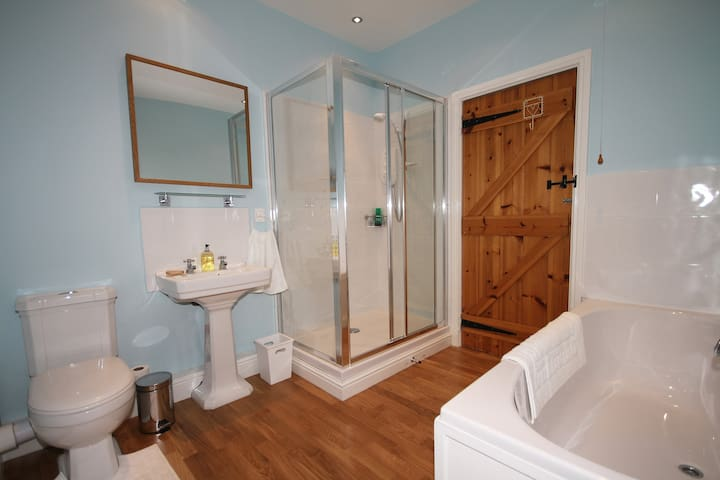 Bathroom with electric shower and bath.