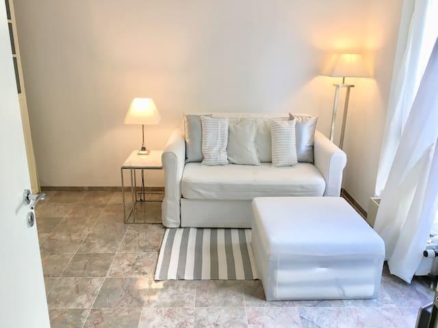 Das Wohnzimmer mit der 1-2Personen 1,20mBettcouch und dem Bettcouchhocker, den man für 1 Einzelperson ausklappen kann.