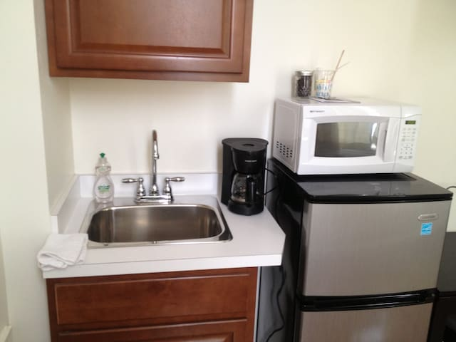 Room contains convenient kitchenette with sink, coffee maker, frig and microwave.
