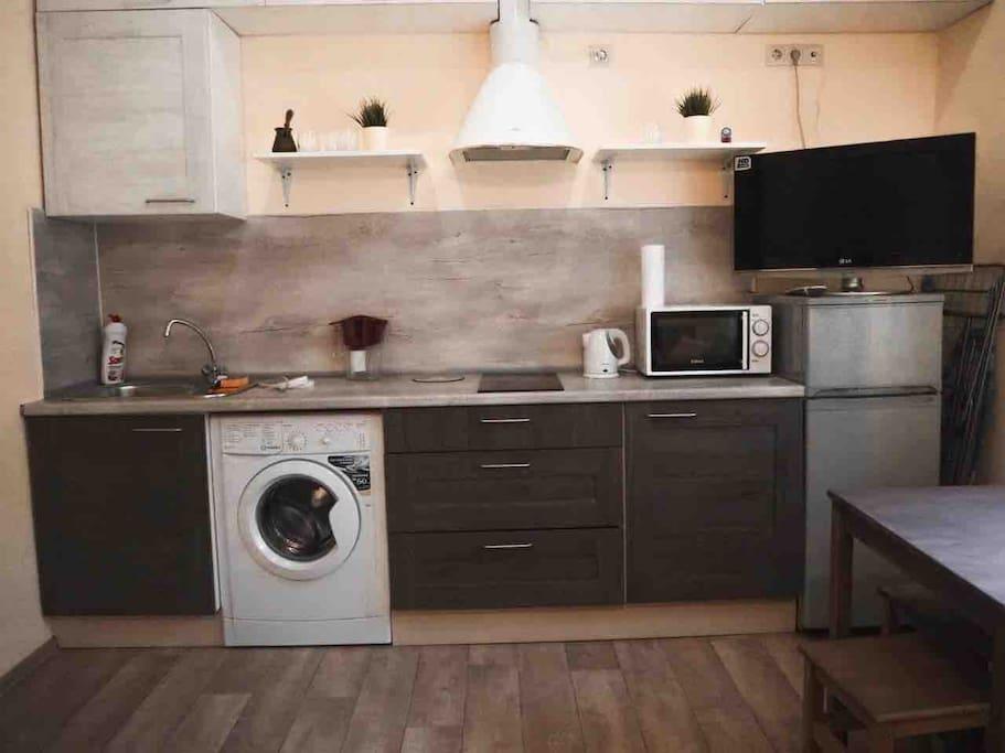 Встроенная кухня с микроволновой печью, варочной панелью и холодильником.