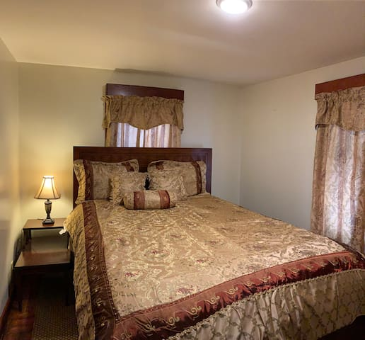 Queen bedroom with wall mounted flatscreen Roku TV, closet and small console table.
