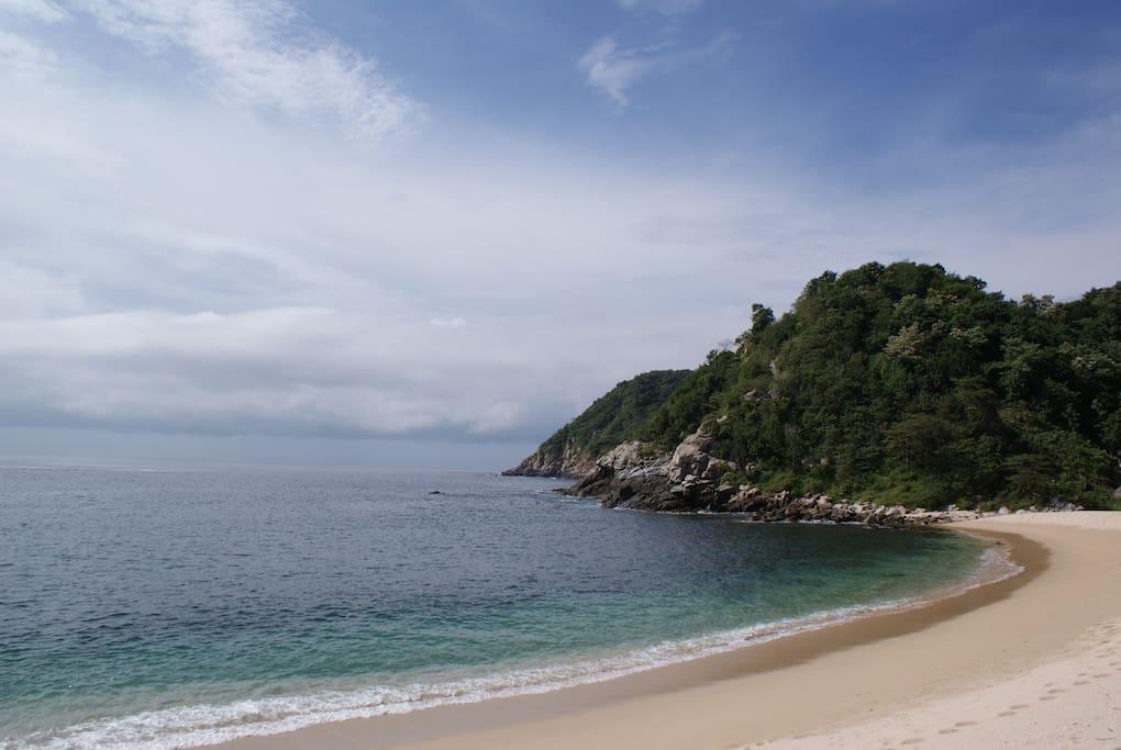 Nace en una playa escondida del Pacífico mexicano, se encuentra rodeada de naturaleza, camuflada entre la selva a los pies de la sierra, se mimetiza en lo verde de la montaña en una playa de arena blanca, tranquila, virgen, con agua color azul turquesa en
