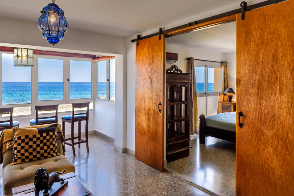 View of the master bedroom through the double doors in the lounge/sala with beautiful views of the ocean