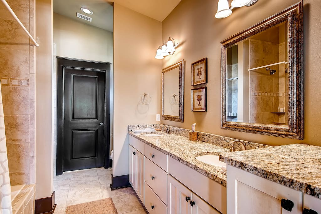 The opulent master bathroom (bedroom #1) has granite counters, double sink, and a nicely tiled tub/shower.