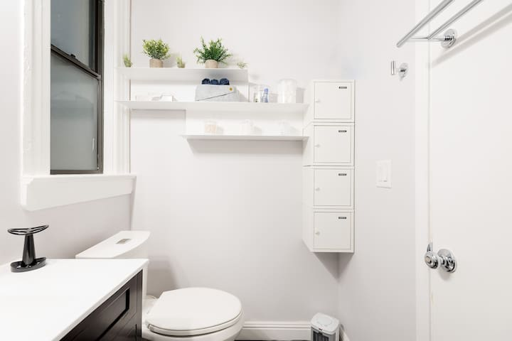 Shared bathroom, fully stocked with guest storage cubbies.