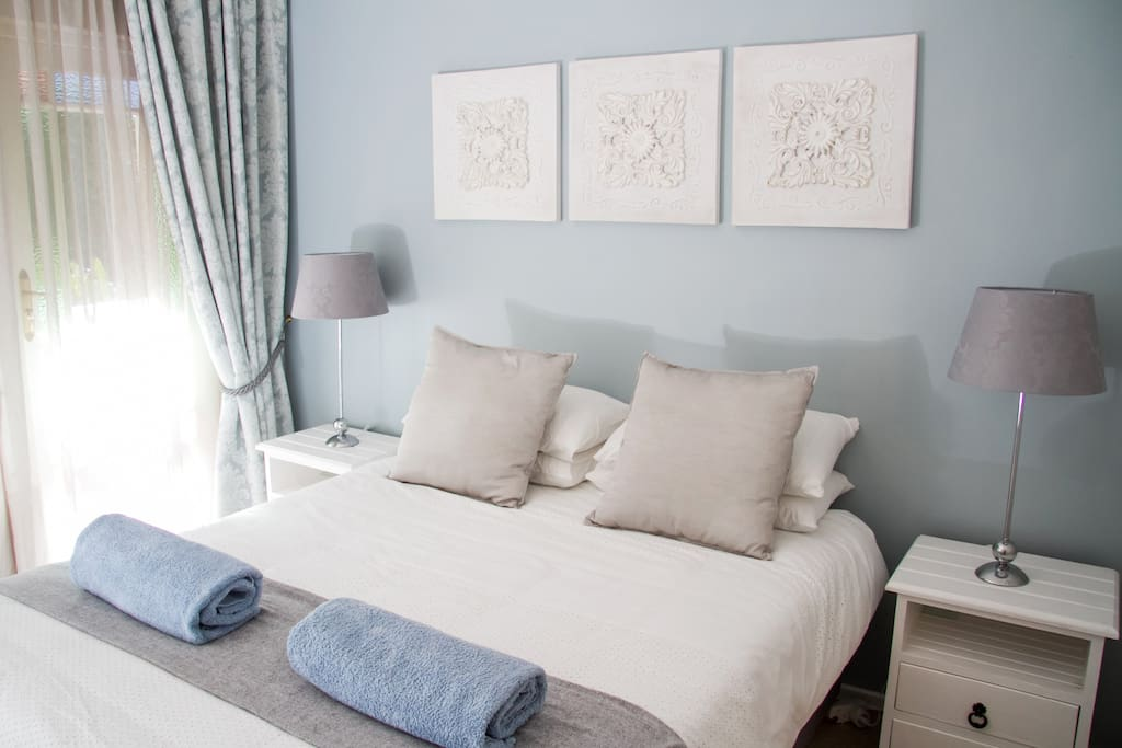 Bedroom 2, decorated in subtle french blues and greys, opens onto the shaded patio.