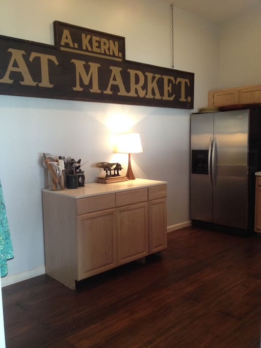 kitchen w/stainless steel appliances + a bar opposite this wall | open to dining + living