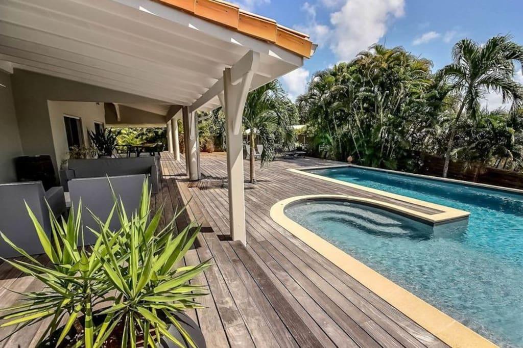 La large piscine bordée d'un deck