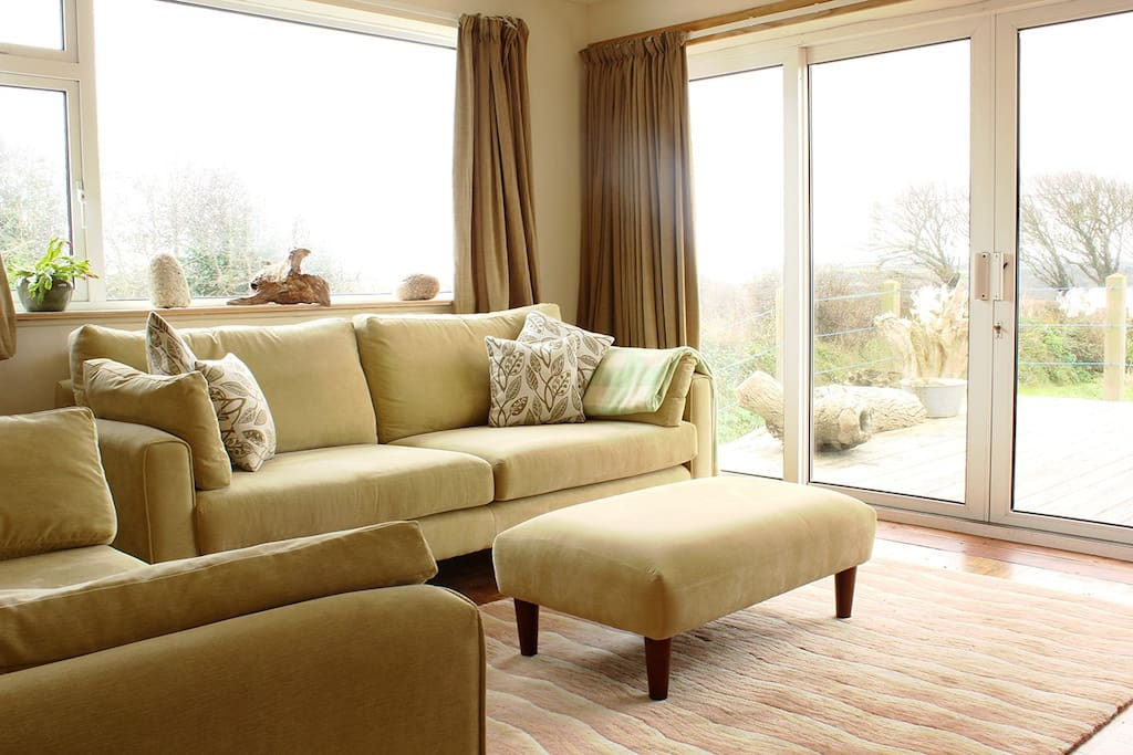 The Living Room with its patio doors has panoramic views that look out across the large garden and over the fields that surround the house. In the garden you'll find a wildflower meadow and a bbq for post-beach sunny evenings.