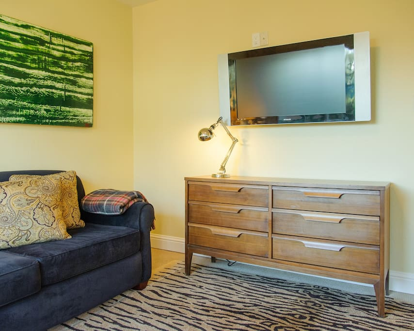 well lit living room has an internet ready large screen tv. also has Directv. plenty of storage in the mid century dresser