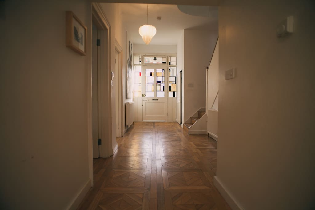 Solid french oak floor throughout the house. Here you see the corridor leading to the fount door which has been designed with antique stained glass.