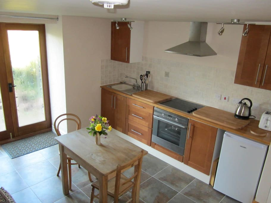 Fully equipped kitchen with French doors to patio and garden.
