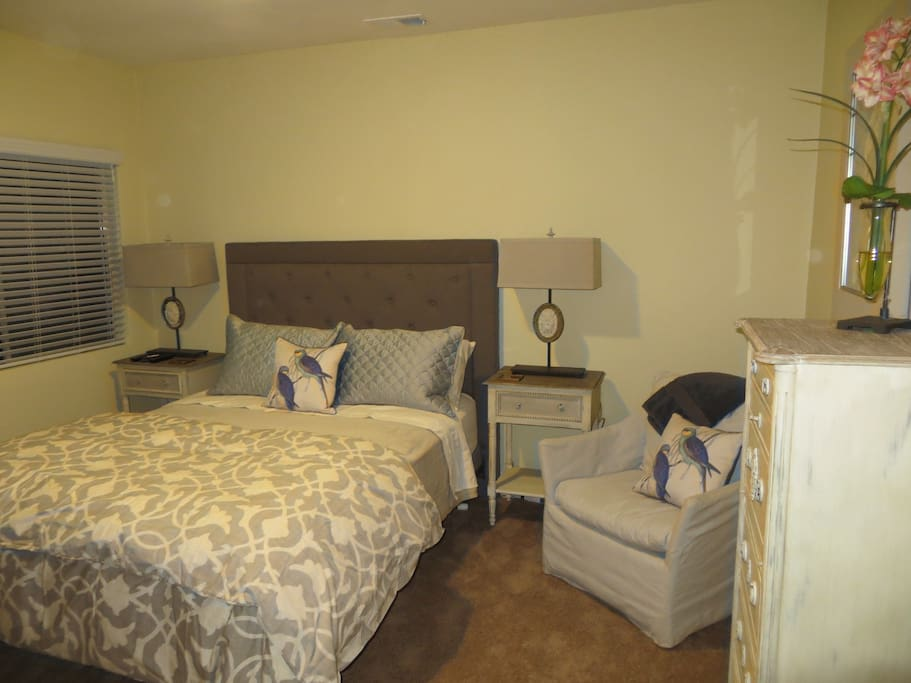 Master bedroom, with Queen bed. It faces a wall-mounted TV