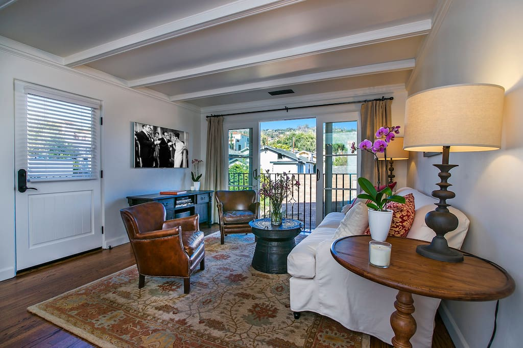 Living room with large flat screen TV with DVD player, sliding doors with view towards Santa Barbara Riviera