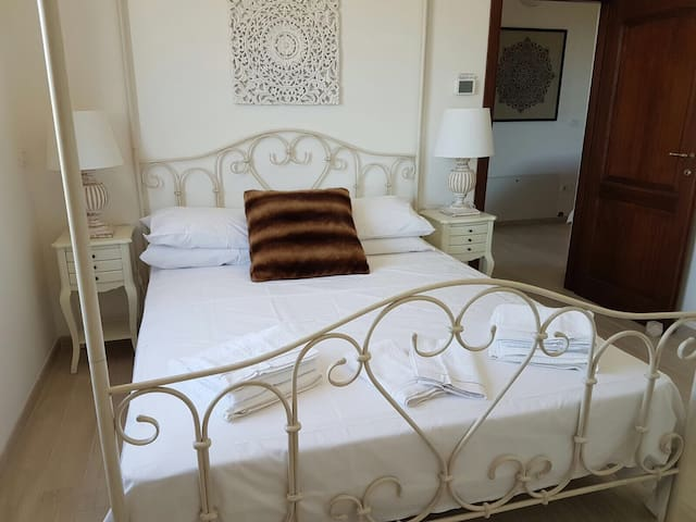 A view of the second bedroom with a double four poster bed, soft furnishings and contemporary wall art.