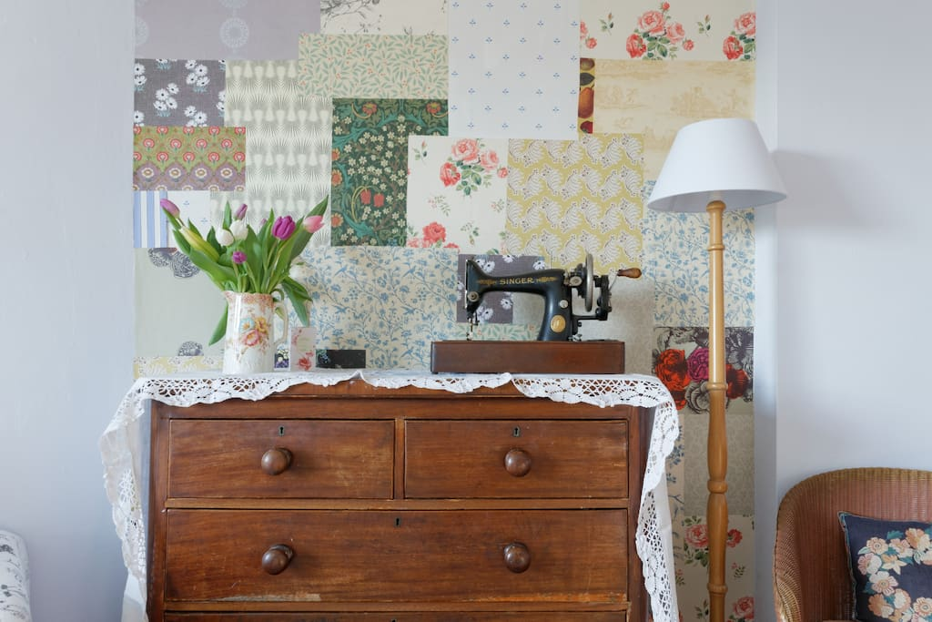 Roomy antique chest of drawers and vintage patterned wallpaper.