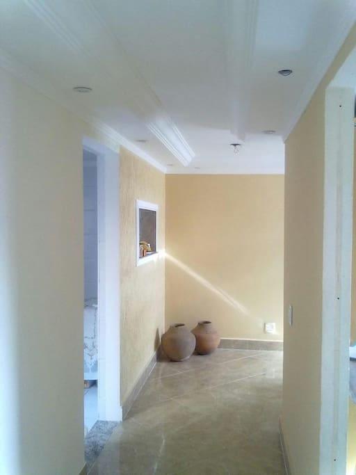 Corredor entre sala e quartos com grande espaço livre.