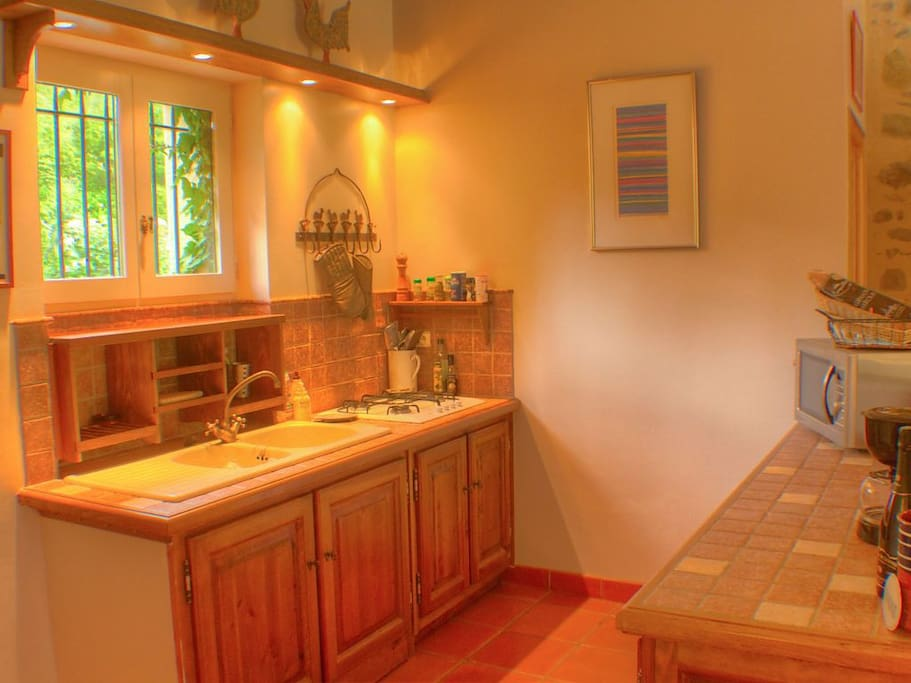 The well-equipped kitchen, overlooking the dining area, has nicely tiled counters, with wood cabinets, fridge, gas stove top, a convection/microwave oven, double sinks, and top quality cooking utensils and tableware.