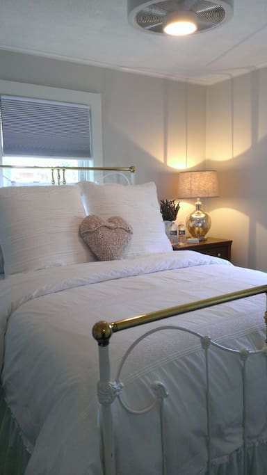 Bedroom 2 is dressed in white and cool beach blue.  Antique Iron Bed