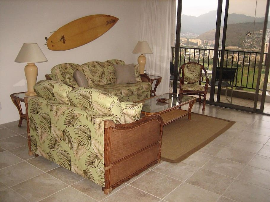 Spacious and comfortable, the living room has a sofa, loveseat, chair, and a sliding door out to the lanai.
