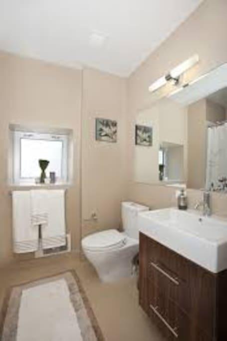 Sparkling bathrooms with custom walnut vanities