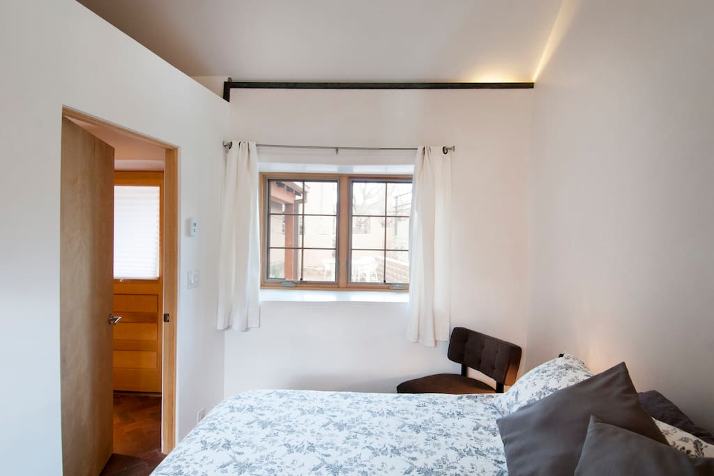 Private Bedroom with King Bed -view through windows are east mountains & front shared courtyard.