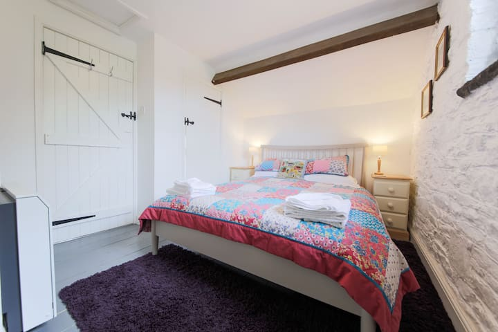 The upstairs bedroom has a king size bed and en-suite bathroom. Bath and hand towels are provided. There is a cupboard and hanging space for clothes plus a small desk with power point.