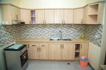 Clean kitchen with a gas stove of four pots and an oven, and plenty of kitchenware for making and serving delicious meals in the cabinets