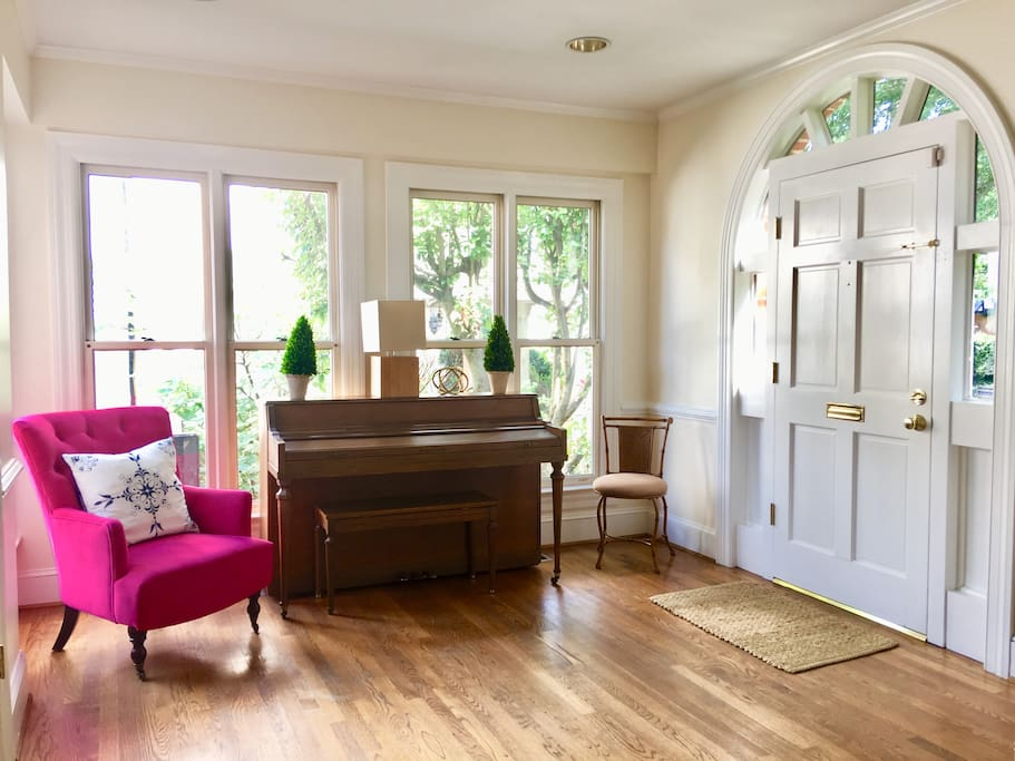 Entry way with piano and comfy chair for reading. Note the beautiful door and hardwood floors.