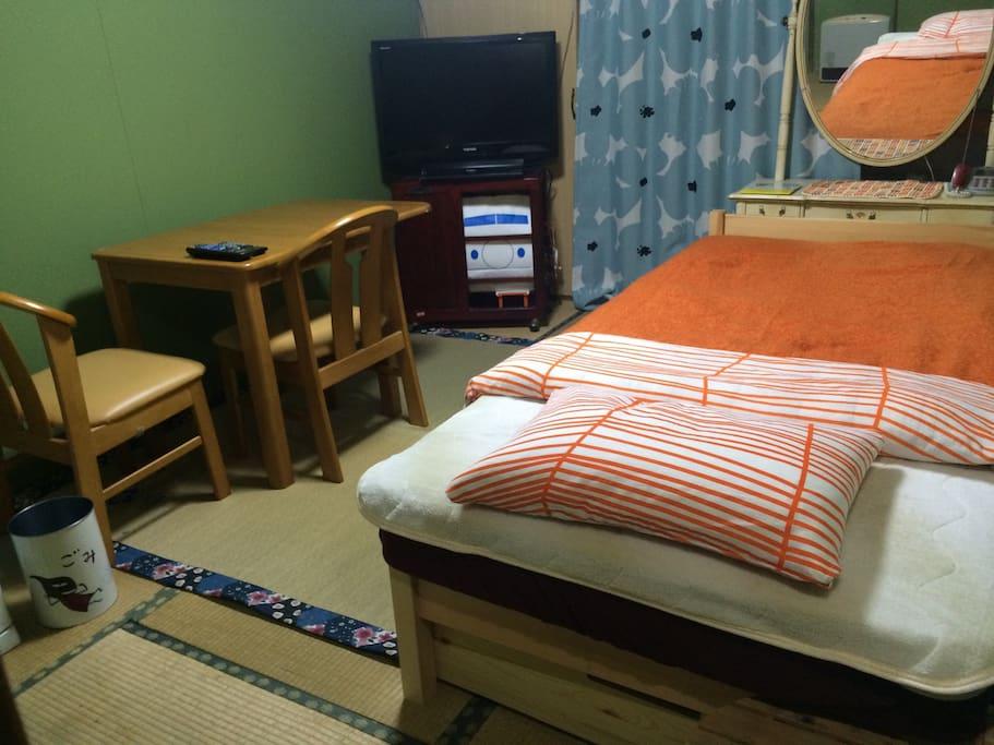 一階 真ん中部屋は居間兼寝室。夏場は西陽がキツいので、カーテン併用してエアコンと扇風機をご利用ください。遅くまでゆっくりしたい方にも嬉しい遮光カーテンです。