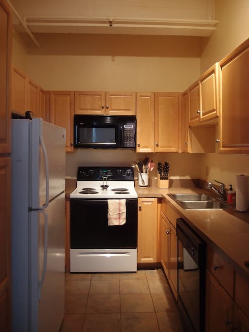 Kitchen with dishwasher, stove, microwave, fridge, and basic cooking/dining essentials.