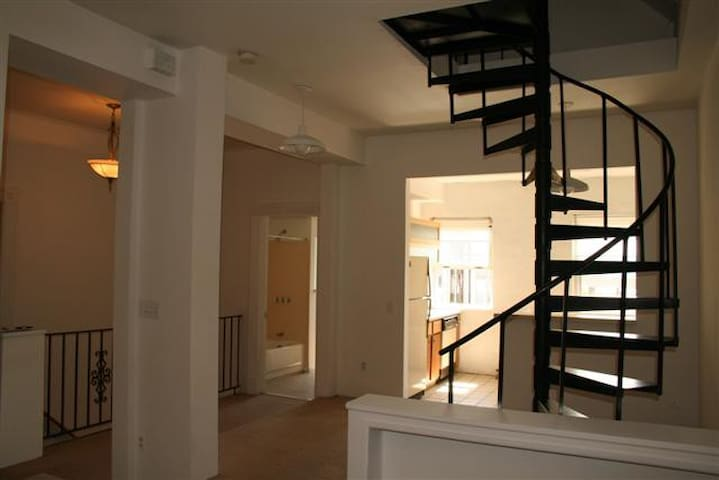 Far corner of picture is Kitchen and dining room (beside spiral stairs).  Spiral staircase leads to bedroom 2 and bathroom 2 and space where airbed is upstairs.