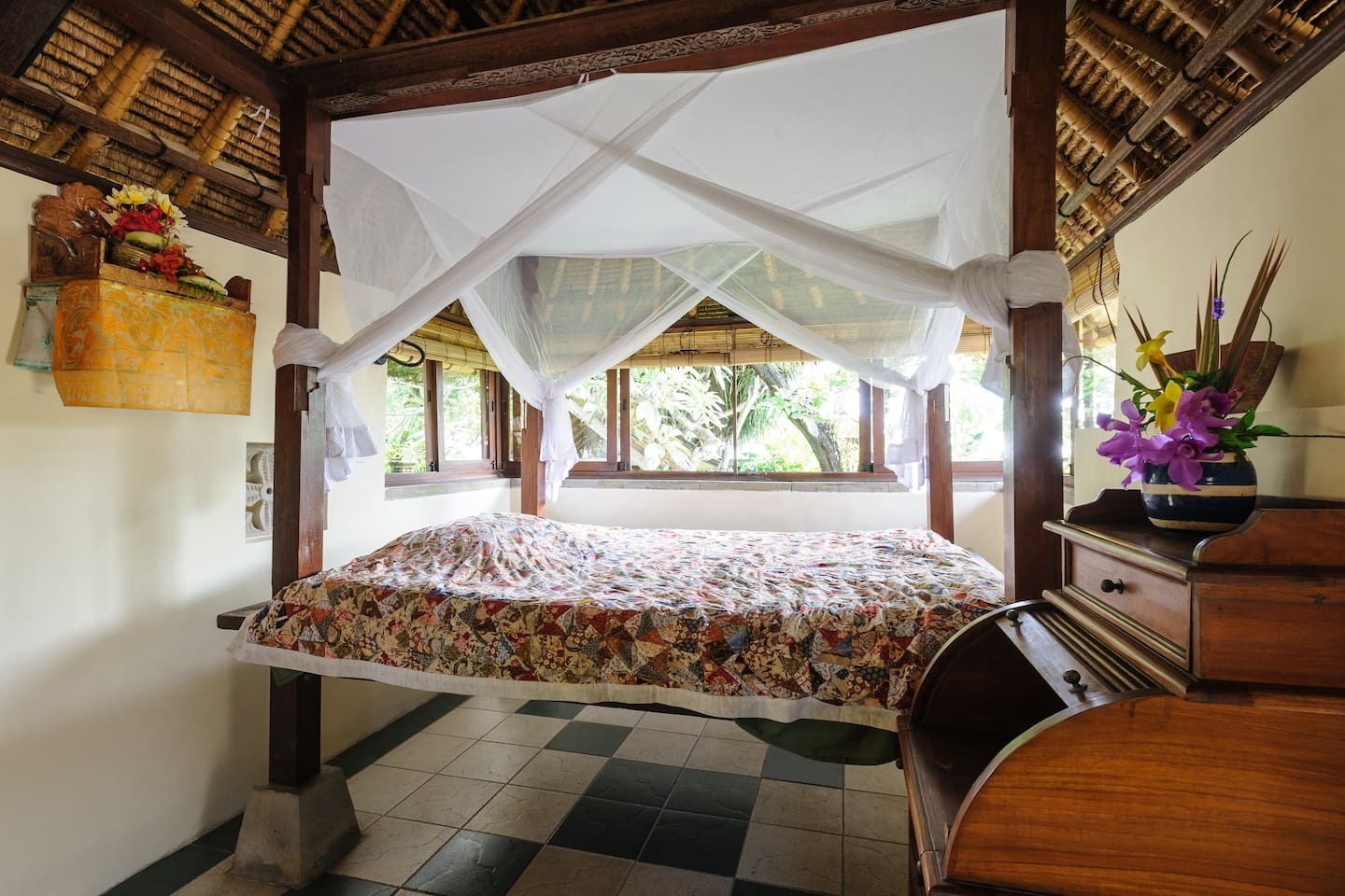 Traditional Balinese four-poster bed with views across the garden, over the wall to the sea