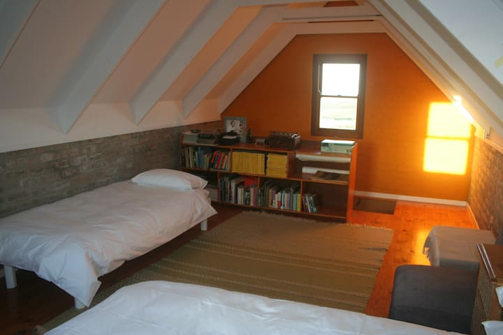 Upstairs, single bed and bookshelf. Facing East.