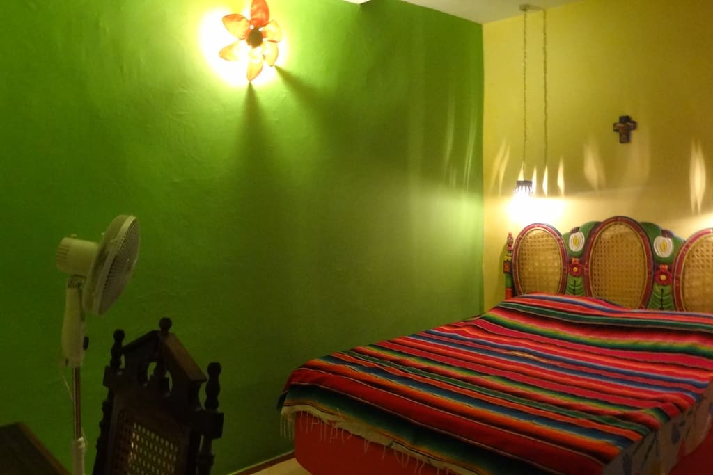 Mexican room with a double bed window is on inside
