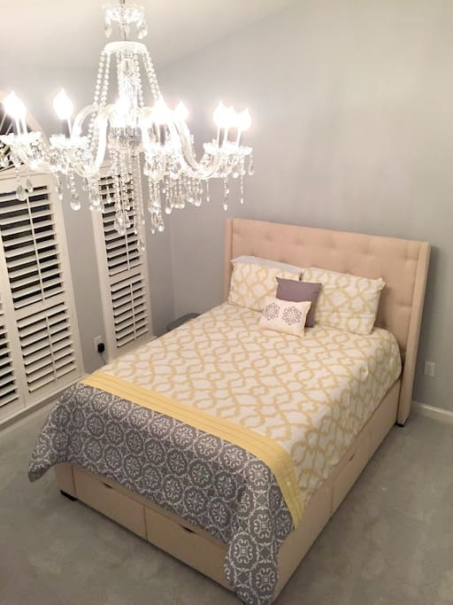 In the master bedroom, a brilliant chandelier provides accent lighting above the queen bed.