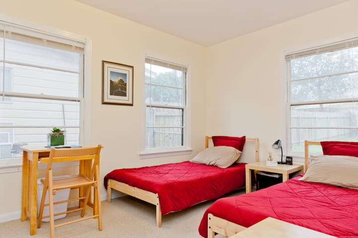 The guest room with two twin beds, desk, tables, lamp, clock and more.
